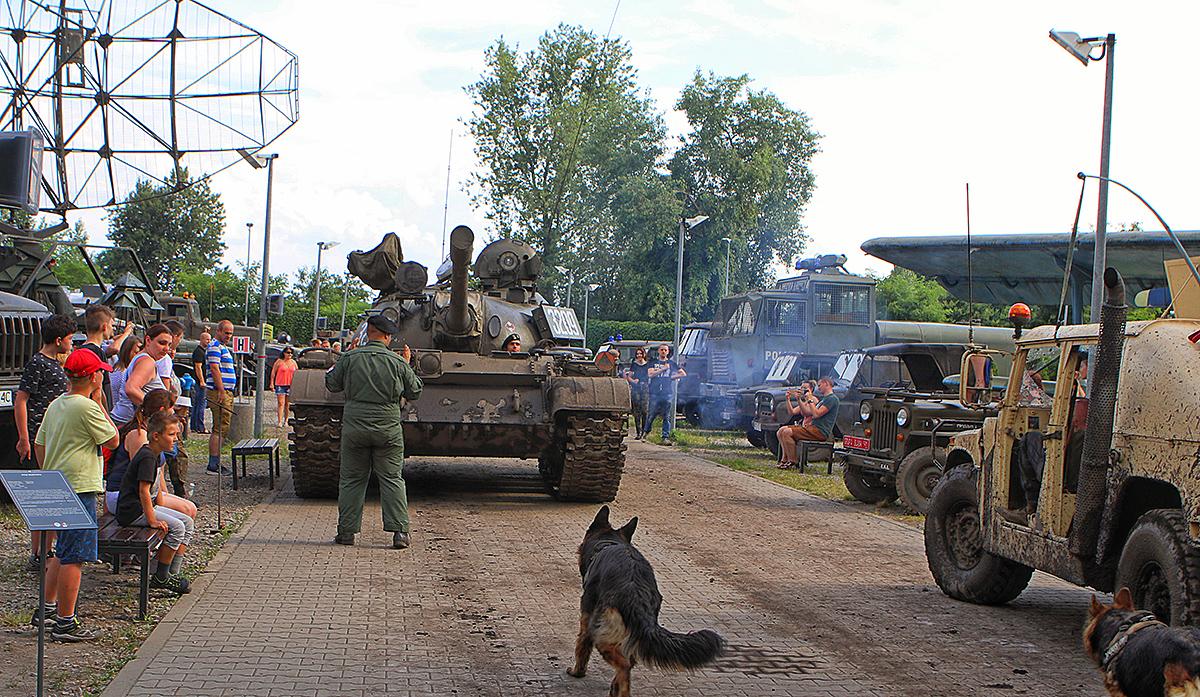Czołg jedzie po alejce Parku Techniki Wojskowej, wokół stoją ludzie i obesrwują